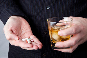 alcoholic-shutter129780437-man-holding-pills-and-glass-of-alcohol