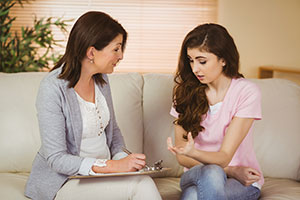 Young woman sitting on couch with therapist