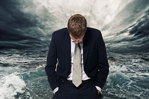 Business man with head down with waves in background